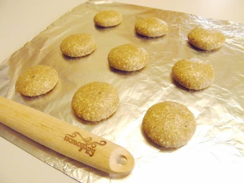 8. Разделите тесто на кусочки, скатайте шарики, приплюсните их для придания овальной формы. Выложите на фольгу и бумагу. Разогрейте духовку до 200 градусов.