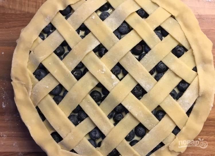 7.Достаньте тесто в пленке из морозильной камеры, раскатайте тонко, нарежьте его полосками. Украсьте пирог полосками из теста.