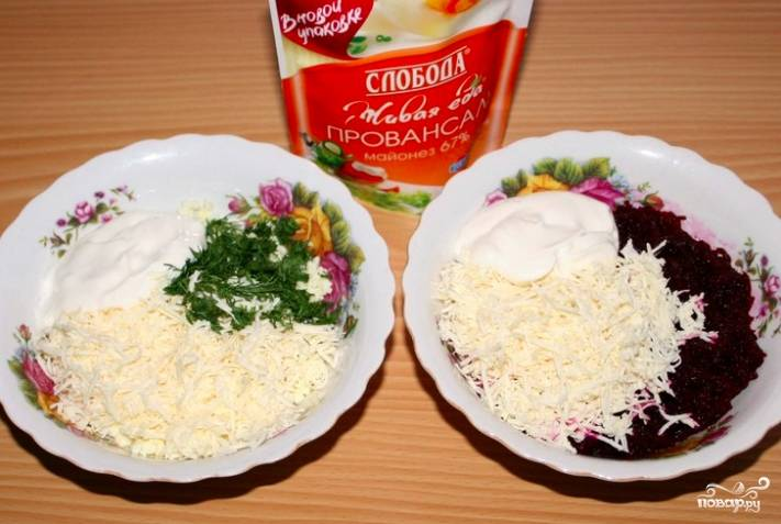 Половину тёртого сыра переложите к яйцам, а вторую половину — к свекле. Добавьте в каждую тарелку по 1 столовой ложки майонеза. Тщательно размешайте. Можно посолить, если хотите.