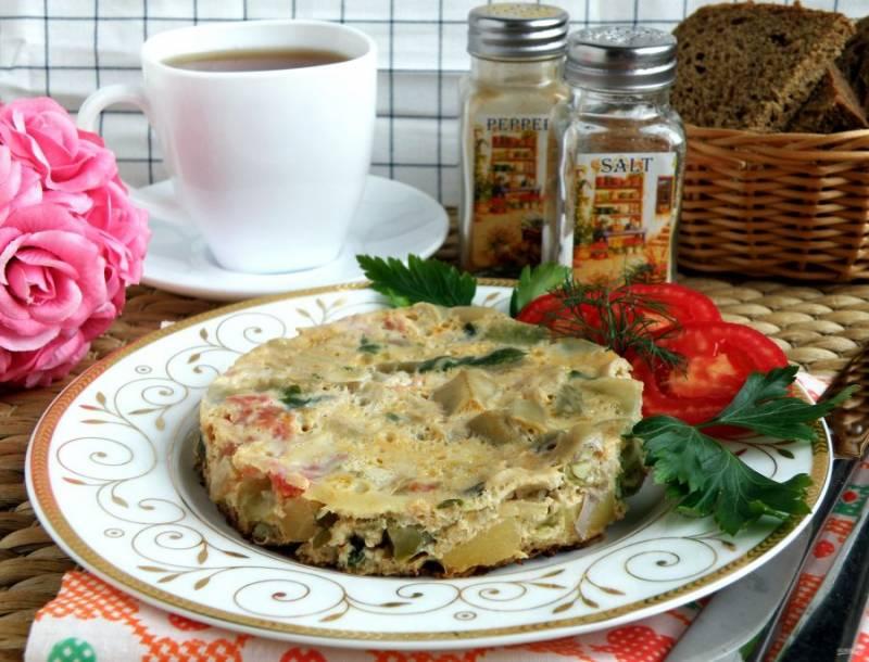 Сервируйте фриттату со свежим хлебом и зеленью. Подайте помидоры и тертый сыр, чтобы едоки могли посыпать им сверху свою порцию по вкусу. Фриттата вкусна и холодной.