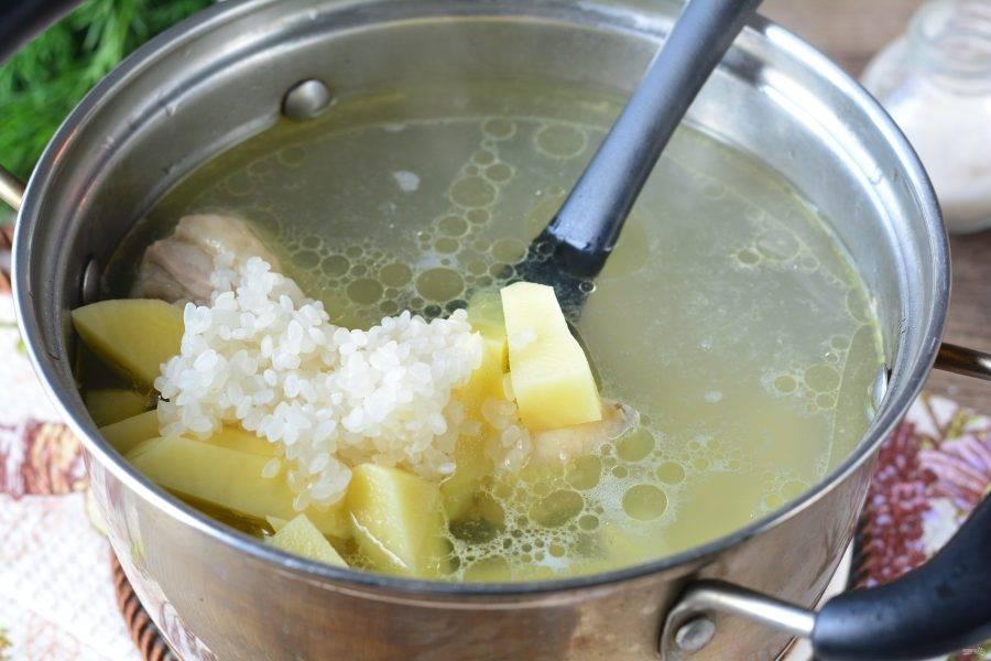 Следом всыпьте в суп промытый рис. Варите суп еще 15 минут на умеренном огне.