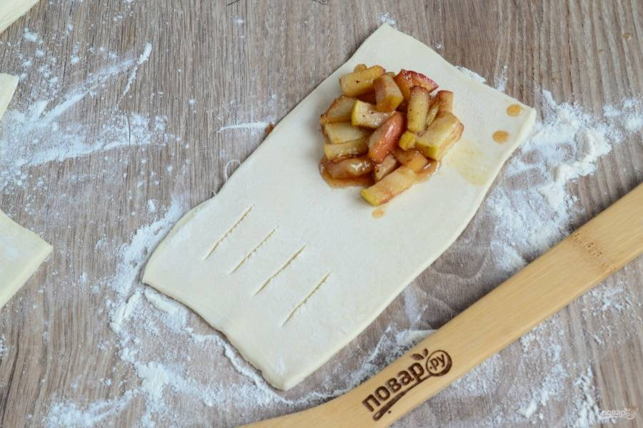 Тесто порежьте на прямоугольники примерно 5 на 10 см. Каждый прямоугольник слегка раскатайте. Условно поделите прямоугольник пополам, на одну половину положите 1 ст. ложку яблочной начинки. На второй половине теста сделайте продольные надрезы.