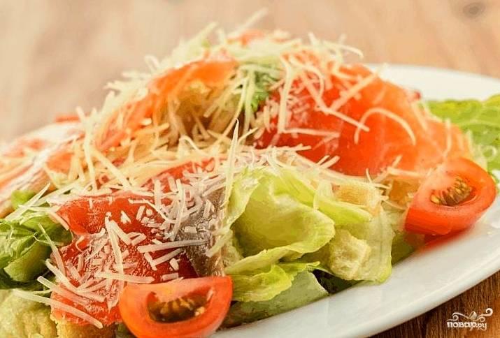 Листья салата осторожно покрыть соусом. Сверху выложить крутоны и лосось. полить оставшимся соусом и посыпать пармезаном. при желании украсить дольками помидоров.