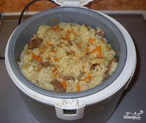 Открыть мультиварку, попробовать рис. если он еще твердоватый - долить немного воды и готовить 10- минут дополнительно. Если плов уже готов, перемешать, вынуть чеснок.