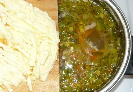 Готовый омлет чуть остудите и порежьте полосочками. Добавьте полоски омлета в суп.