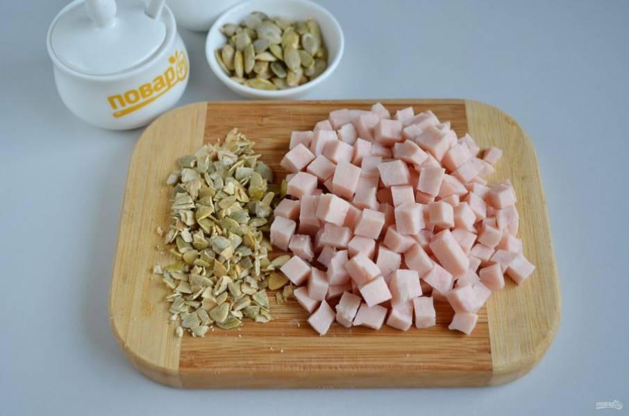 7. Ветчину порежьте кубиками. Часть тыквенных семечек оставьте для украшения булочек, остальные порубите ножом крупно, они пойдут в тесто.