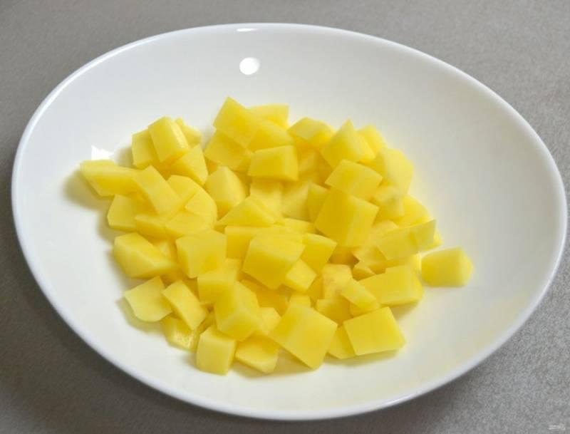 Нарежьте кубиком картофель.