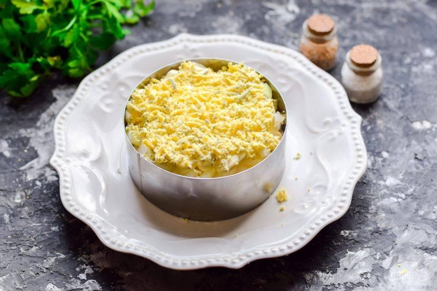 """Куриные желтки натрите на мелкой терке и посыпьте салат. Готовый салат """"Мимоза"""" с кальмарами пропитайте час и подавайте к столу."""