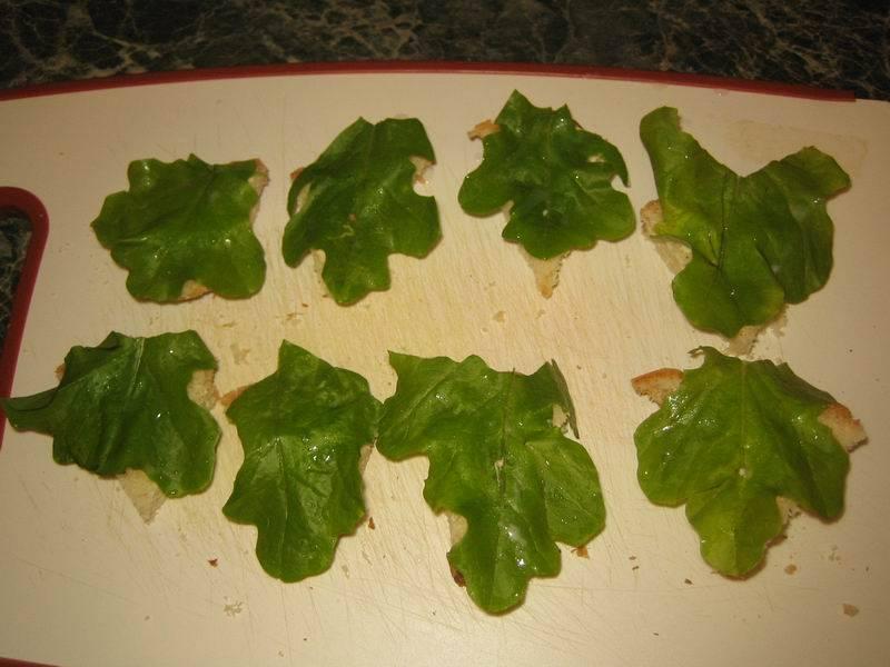 Промойте листья салата, порвите руками на небольшие кусочки (по размеру — чуть больше кусочков хлеба). Выложите сверху.