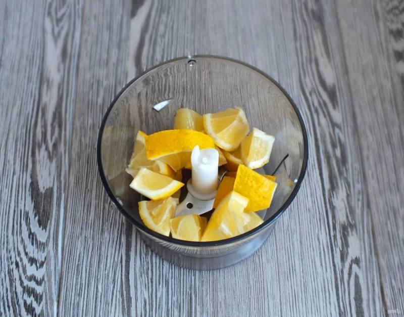 Пока тесто находится в холодильнике, сделайте начинку. Лимон ошпарьте кипятком. Разрежьте на кусочки, удалите косточки и переложите  в блендер. Пробейте как можно мельче.
