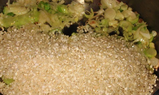 В отдельной глубокой сковороде на растительном масле обжарьте измельченный лук. Добавьте рис, обжаривайте 3 минуты.