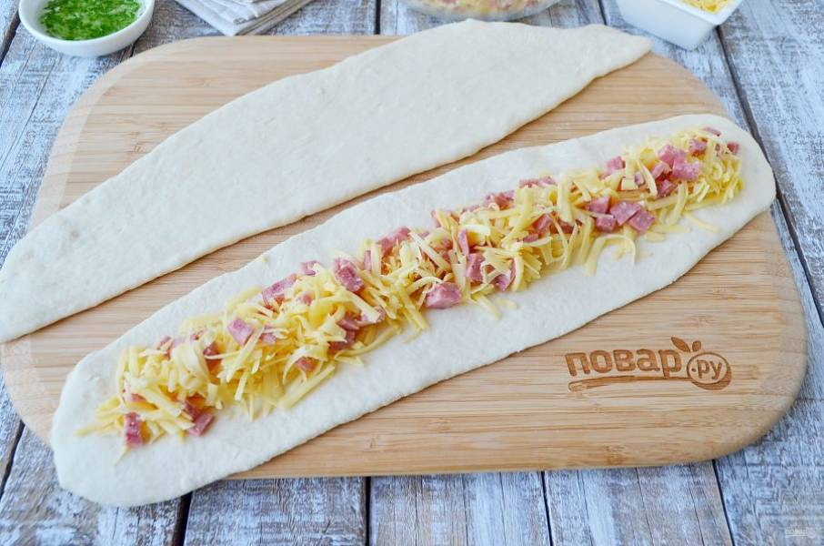 Тесто (300г) разделите на 6 частей, каждую раскатайте в длинную тонкую полоску. На каждую полоску положите начинку из сыра и колбасы.