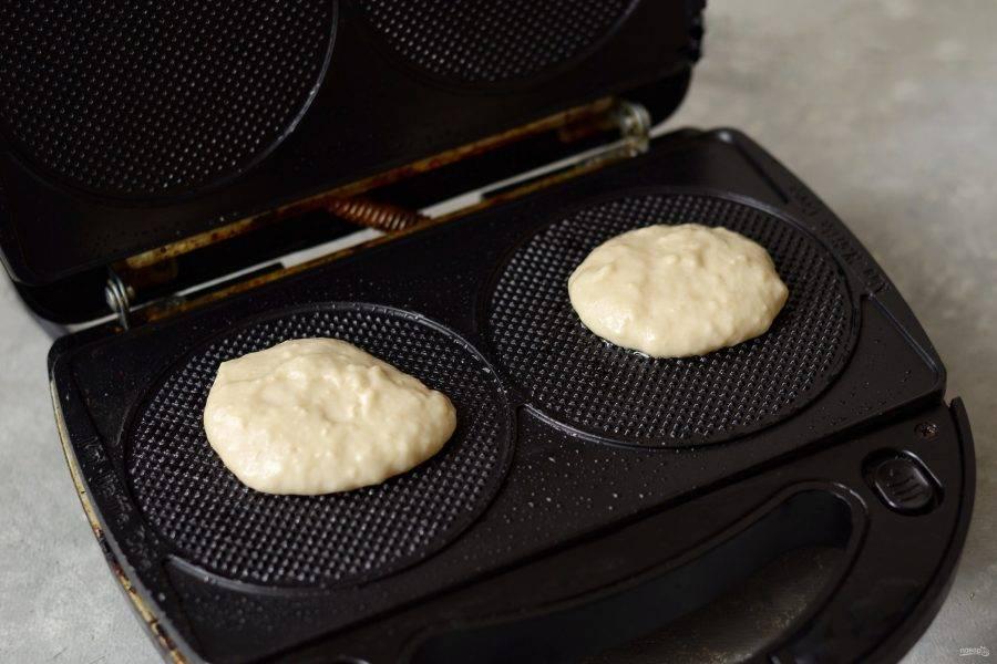 Разогрейте вафельницу, смажьте форму маслом и выложите примерно 1 ст.л. на каждую половинку. Выпекайте вафли 5 минут.