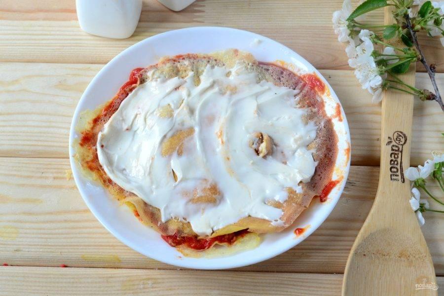 Сверху накройте вторым омлетом, который смажьте сливочным сыром, смешанным с орегано, черным молотым перцем и парой столовых ложек молока.
