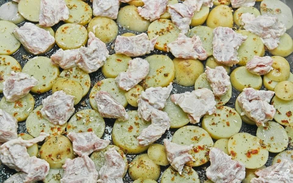 7. Когда картошка слегка испечется, достаньте противень и сверху выложите свинину в соусе. Равномерно все распределите. Поставьте противень снова в духовку на 15 минут.