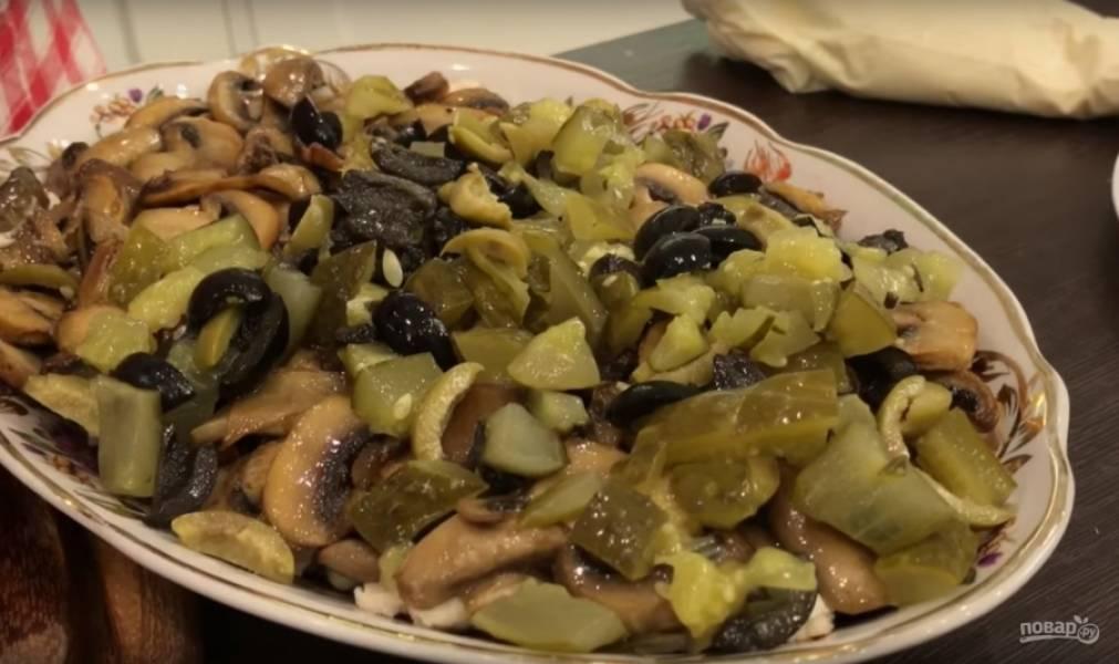 Оливки с огурцами перемешайте и выложите следующим слоем на тарелку. Также можно добавлять каперсы или оливки, начиненные каперсами или лимоном.