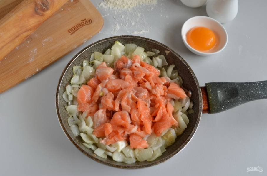 Семгу порежьте небольшими кусочками, добавьте её к луку и обжарьте до изменения цвета рыбы. Добавьте в процессе пару щепоток соли.