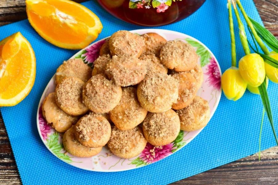 Каждое печенье обмакните в подготовленный сироп и сверху посыпьте измельченными грецкими орешками.