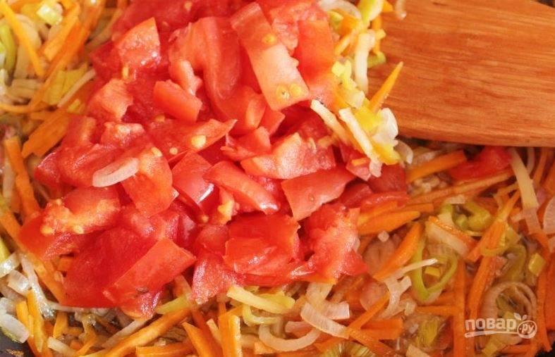 Томаты вымойте и сделайте на них надрезы остром ножом так, чтобы получился крест. Обдайте помидоры крутым кипятком и снимите с них кожицу. Нарежьте томаты кубиками и добавьте к остальным овощам. Томите еще пять минут.