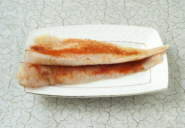 Сделайте надрезы с одной стороны каждого куска филе. Затем натрите рыбу смесью соли, перца и паприки. Положите филе одно на другое, для лучшей пропитки.