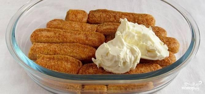 3. Печенье обмакните в пропитку. Сделайте это очень быстро и только одной (сахарной) стороной. Выложите в подготовленную емкость сухой стороной вниз. Сверху пропитанного слоя нанесите крем.