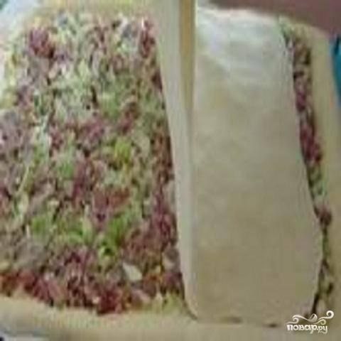 2.Готовое тесто разделить на две неравные части. Большую часть теста раскатать  и выложить на противень.  Перемешать жареную капусту с мясным фаршем и выложить начинку на тесто.