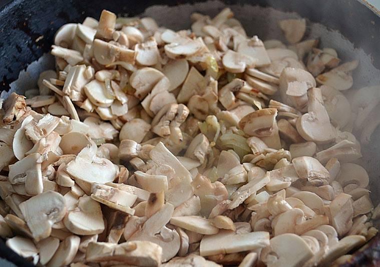 Затем разогреваем в сковороде немного растительного масла и обжариваем на нем измельченный лук и нарезанные грибы.