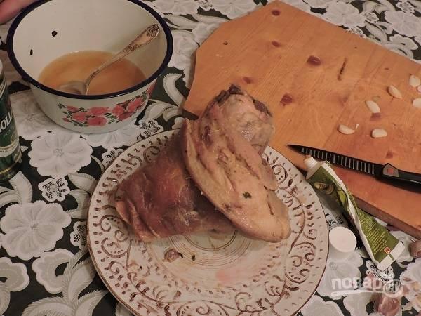 8. Очистите чеснок, нашпигуйте рульку и отправьте в разогретую духовку. Запекайте около 1.5 часов при температуре 180 градусов. В процессе поливайте рульку медово-пивным соусом.