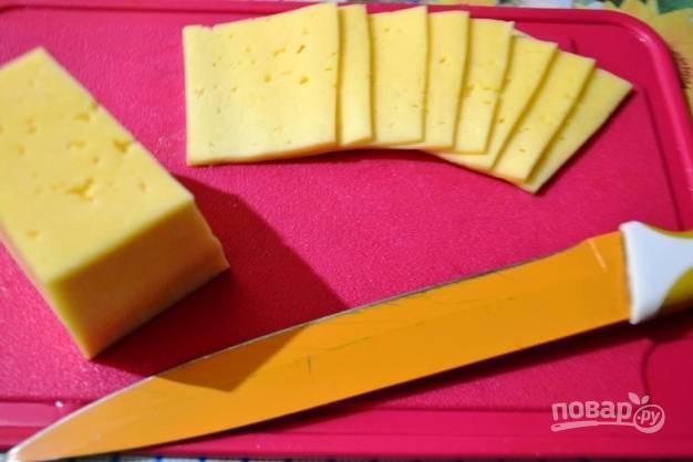 Тем временем можно нарезать твердый сыр на тонкие прямоугольные ломтики.