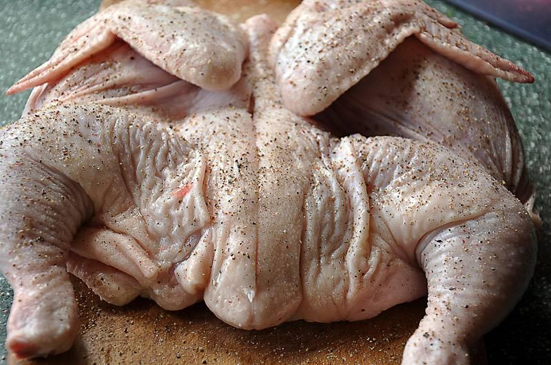 Цыпленка разрежьте по грудке. По позвоночнику сделайте продольный надрез. Посолите и поперчите.