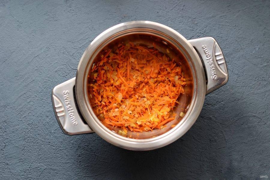 Затем добавьте тертую морковь. Тушите все вместе ещё 3-5 минут.