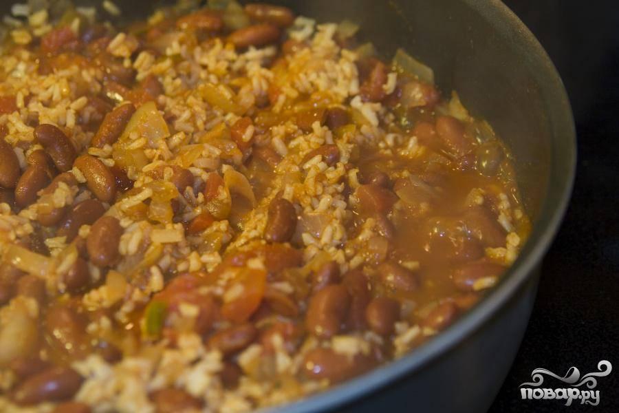 Ослабьте огонь, добавьте помидоры с соком, порошок чили и сальсу. Хорошенько перемешайте. Варить до густой консистенции. Добавить рис, перемешать. Снять с огня и посыпать тертым сыром.
