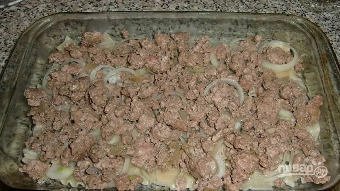 3. Остальной лук с чесноком и мясом пропустите через мясорубку. Выложите фарш на сковороду с разогретым растительным маслом, обжарьте минут 7-10 и переложите в форму. Подсолите фарш по вкусу и добавьте специи при желании.