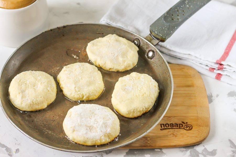 Прогрейте растительное или сливочное масло на сковороде, выложите в него заготовку сырника. Приготовьте и другие заготовки таким же образом, выложите в масло и обжарьте с одной стороны примерно 1-2 минуты.
