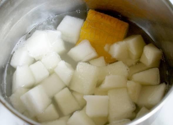 В кастрюлю наливаем воду, добавляем сахар и доводим массу до кипения, выкладываем в кипящую воду дыню вместе с корочкой, варим все в течение 5-10 минут, в зависимости от твердости дыни.