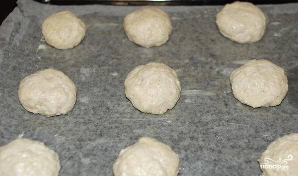 2. Должно получиться густое тесто. Оставьте его охлаждаться в холодильник на полчаса. Затем разделайте тесто на одинакового размера шарики и выложите на застеленный пергаментной бумагой противень.