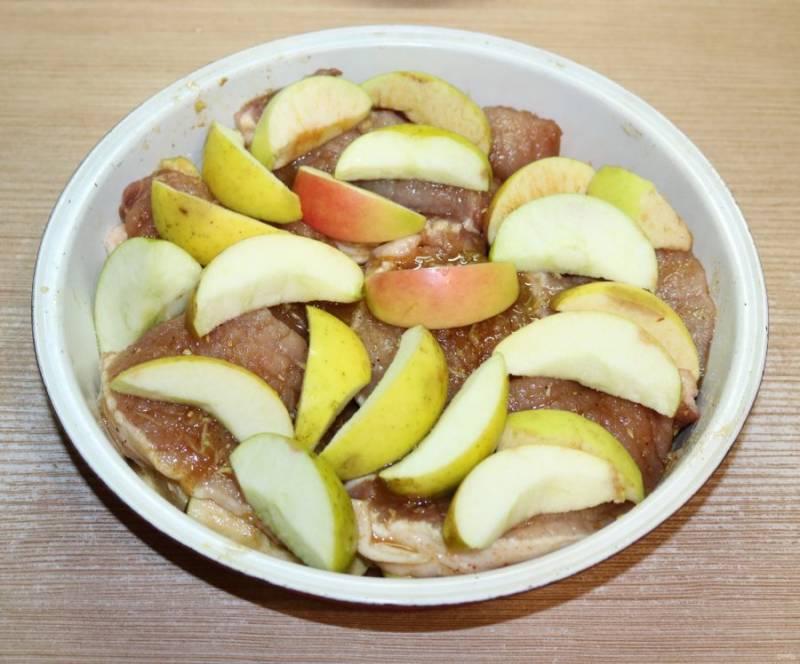 На мясо выложите оставшиеся яблоки и полейте смесью масла, лимонного сока и сахара.
