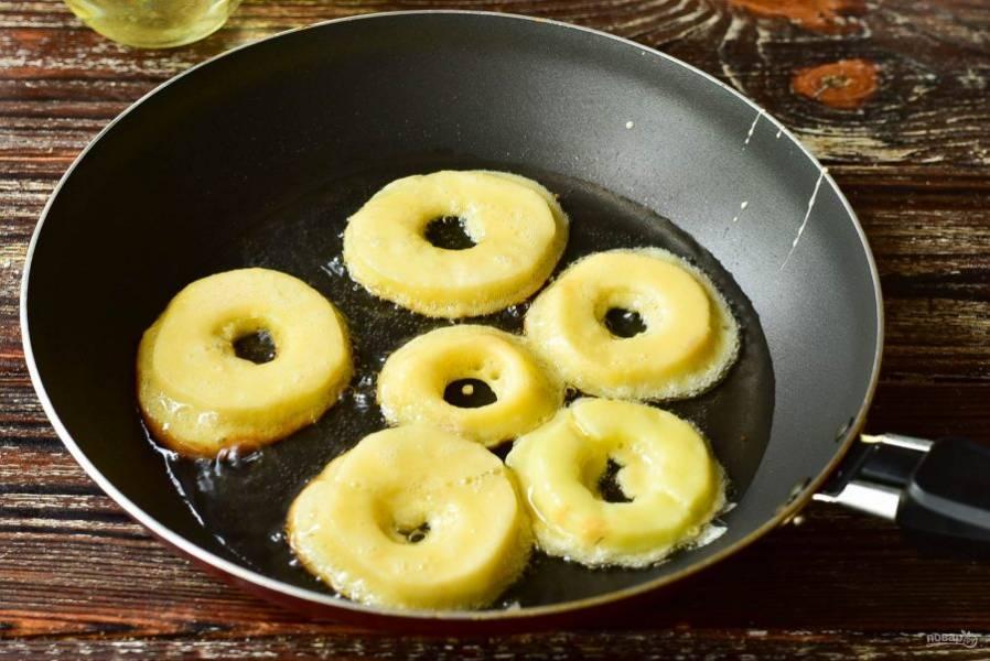 В сковороду с разогретым растительным маслом выложите кружочки яблок.