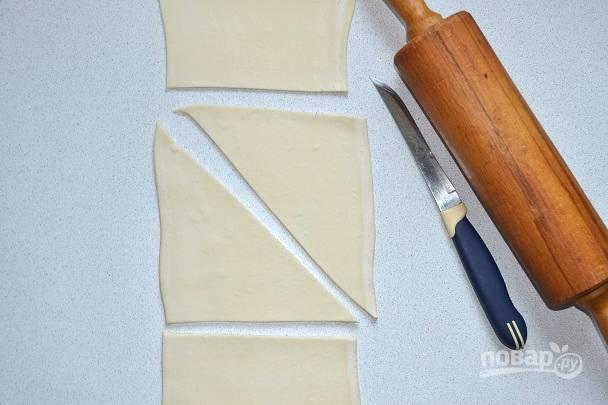Тесто раскатайте в пласт и нарежьте на треугольники.