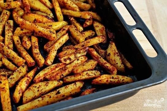 Перекладываем картофель на смазанный маслом противень. Ставим в разогретую до 220 градусов духовку и запекаем 40 минут. Каждые 10 минут картофель перемешиваем и переворачиваем, чтобы равномерно запекался.