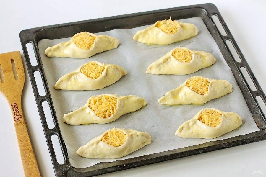 Переложите заготовки на противень, застеленный пергаментом, смажьте взбитым желтком и запекайте в духовке при температуре 180-200 градусов около 20-25 минут.