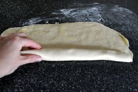 3. Затем сложите один лист на другой, и снова смажьте маслом. Аккуратно сверните его рулетом.
