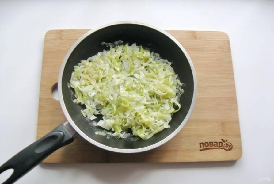 Налейте 20 мл. подсолнечного масла и тушите лук с капустой до мягкости 10 минут, периодически перемешивая.