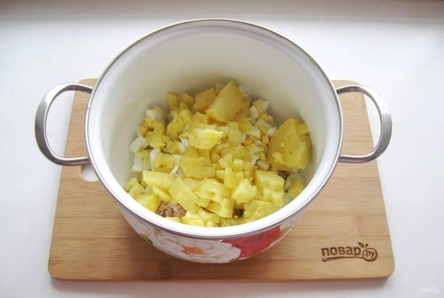 Картофель сварите, охладите и мелко нарежьте. Добавьте в кастрюлю.
