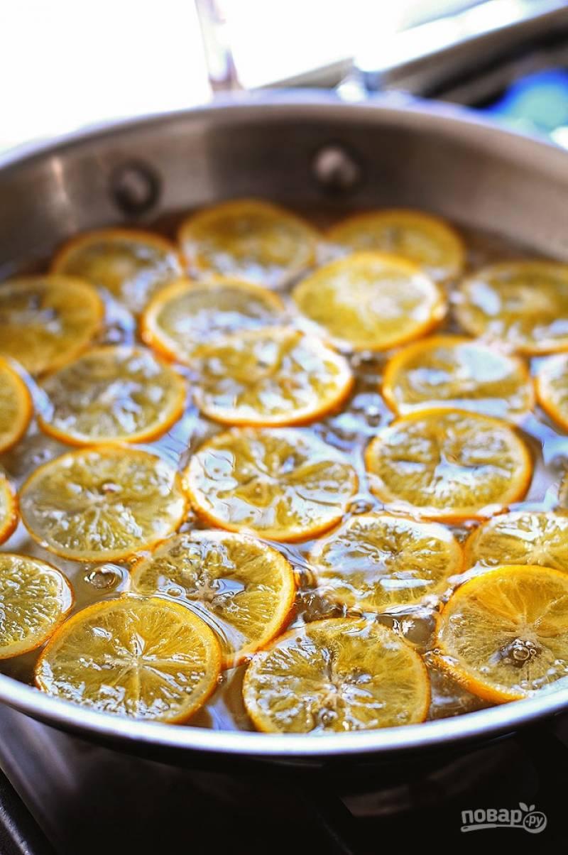 В кастрюлю влейте один стакан воды и добавьте сахар. Варите пока сироп не станет густым, примерно 10 минут. Добавьте лимоны и варите в течении часа на медленном огне, не доводя до кипения.
