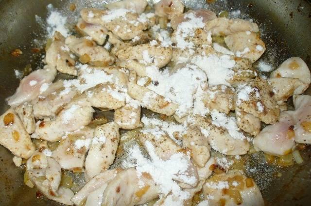 Посыпаем курицу с луком мукой и обжариваем помешивая 1-2 минуты.