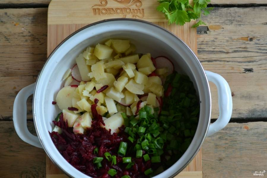 Свеклу натрите на крупной терке, отваренный картофель порежьте кубиком, зеленый лук измельчите. Все ингредиенты соедените в миске и перемешайте.