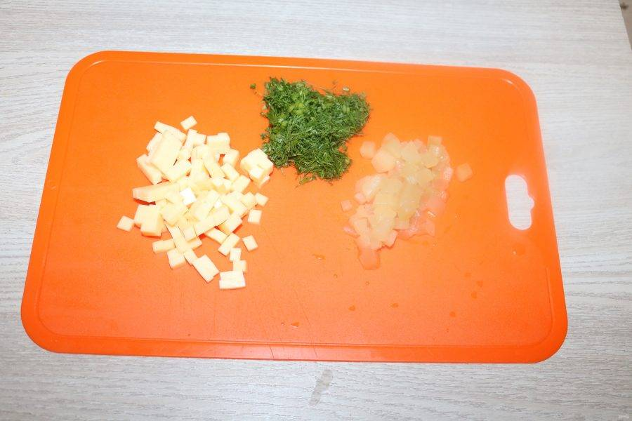 Сыр и ананасы нарежьте кубиками, зелень мелко нарубите.