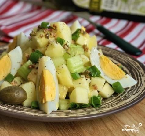 4. Все подготовленные ингредиенты салата соедините в виде аккуратной горки. По вкусу добавьте соль и перец. Заправьте оливковым маслом. Сверху выложите кусочки яиц. Дополнительно оформите салат несколькими каперсами, зеленым луком, сельдереем.