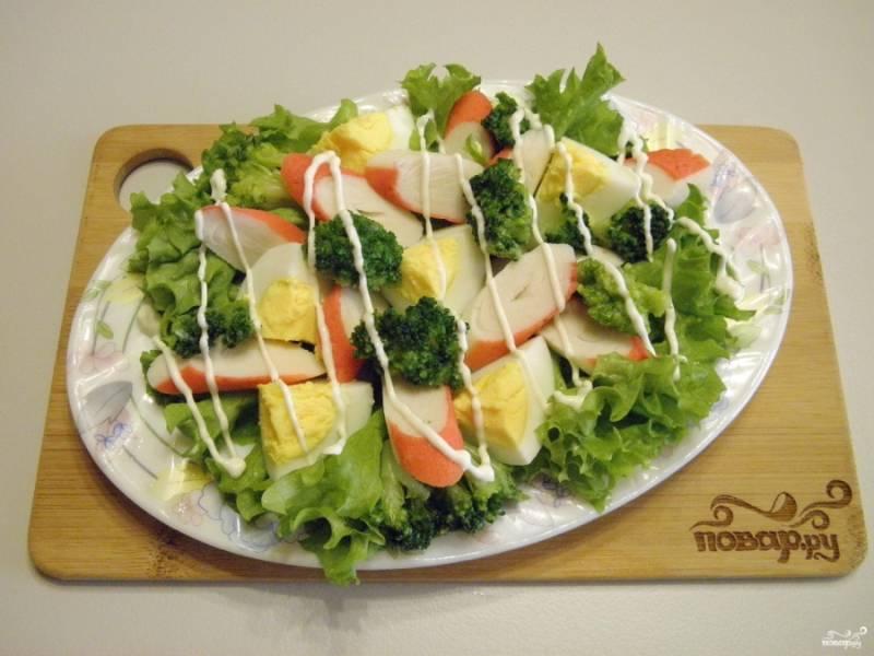 Разложите капусту брокколи. Посыпьте солью и орегано. Сделайте майонезную сеточку. Салат готов, приятного аппетита!